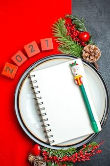 Vista vertical do fundo do ano novo com o caderno espiral no prato de jantar acessórios de decoração ramos de abeto e números em um guardanapo vermelho sobre uma mesa preta