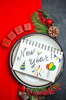Vista vertical do plano de fundo de ano novo com caderno com desenhos de ano novo em um prato de jantar acessórios de decoração ramos de abeto e números em um guardanapo vermelho sobre uma mesa preta