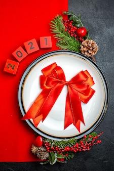 Vista vertical do plano de fundo de ano novo com fita vermelha em acessórios de decoração de prato de jantar ramos de abeto e números em um guardanapo vermelho em uma mesa preta