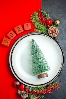 Vista vertical do plano de fundo do ano novo com árvore de natal acessórios de decoração de prato de jantar ramos de abeto e números em um guardanapo vermelho sobre uma mesa preta
