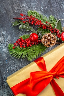 Vista vertical do presente de ano novo com fita vermelha e enfeites de acessórios na superfície escura