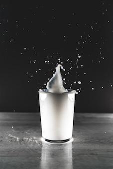 Vista vertical em tons de cinza de um respingo de líquido branco em um copo de vidro