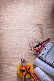 Vista vertical ferramentas elétricas multímetro testador pinças chave de fenda rolo fita isolante modelo organizado copyspace na placa de madeira