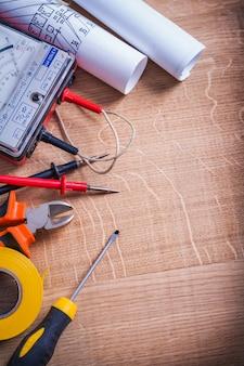 Vista vertical ferramentas elétricas pinças multímetro testador chave de fenda rolo fita isolante na placa de madeira