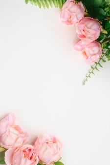 Vista vertical superior de flores artificiais de peônias rosa e folhas de samambaia verde sobre fundo branco em branco