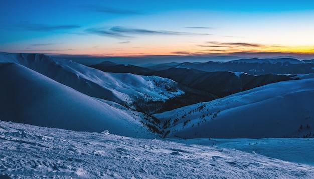 Vistas deslumbrantes sobre as encostas da estância de esqui após o pôr-do-sol no final da tarde.