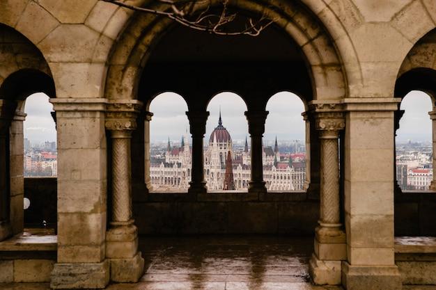 Vistas do parlamento húngaro através das muralhas do castelo de budapeste.