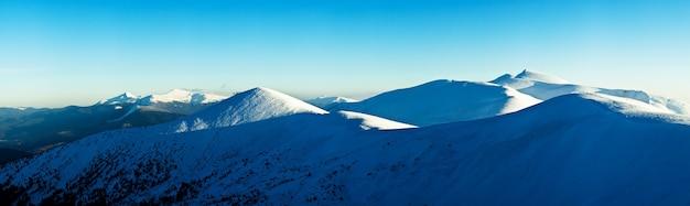 Vistas hipnotizantes de cadeias de montanhas cobertas de neve com o pôr do sol e o céu nublado ao fundo