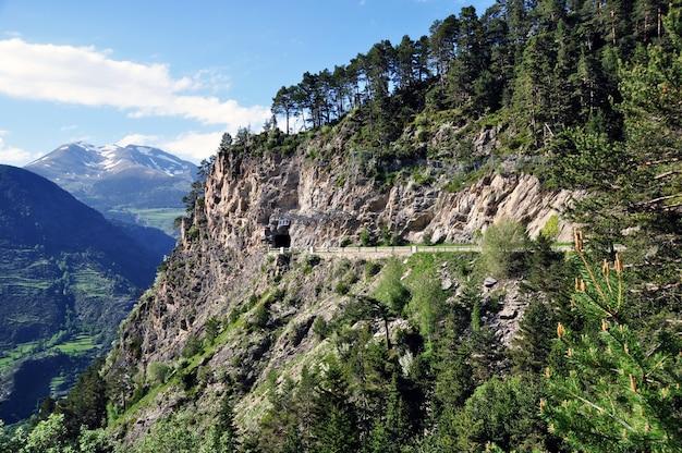 Vistas panorâmicas das montanhas com penhascos íngremes e da estrada que leva ao túnel