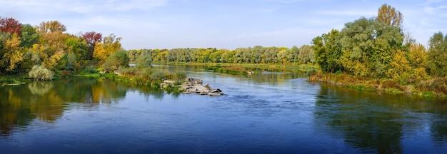 Vistas panorâmicas de rio. floresta de outono na margem. um céu claro e sem nuvens.