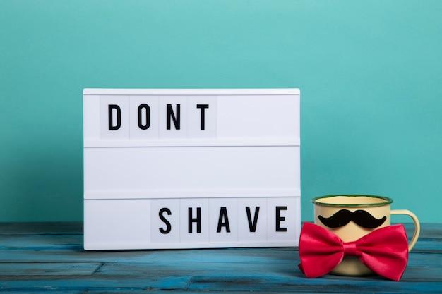 Visual lightbox com as palavras não se barbeia e um copo com bigode e gravata vermelha sobre madeira azul e azul vintage