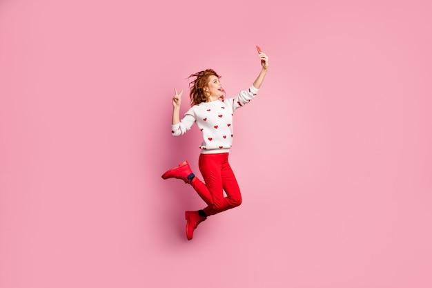 Visualização de corpo inteiro de uma bela garota atraente funky sortuda alegre raposa pulando tomando selfie de célula mostrando o sinal de v se divertindo