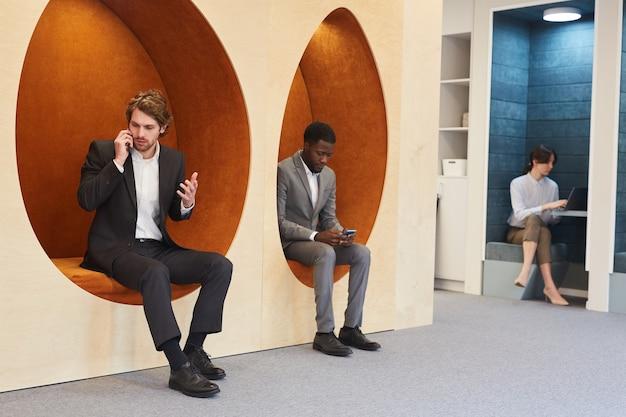 Visualização de corpo inteiro em grupo multiétnico de executivos trabalhando no interior contemporâneo de um escritório ou centro de coworking, copie o espaço