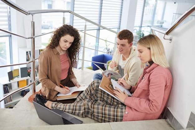 Visualização de corpo inteiro em um grupo de alunos sentados nas escadas da faculdade e trabalhando juntos na lição de casa,