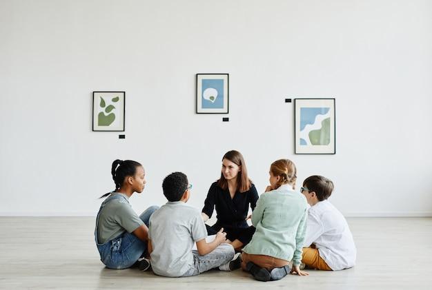 Visualização de corpo inteiro em um grupo diversificado de crianças sentadas em círculo durante a aula na galeria de arte, copie o espaço