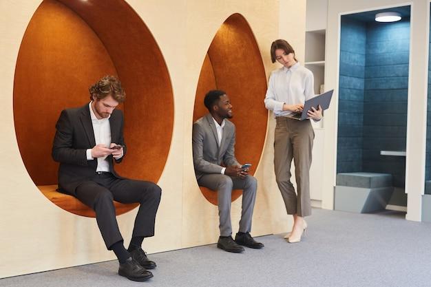 Visualização de corpo inteiro em um grupo multiétnico de jovens empresários trabalhando no interior contemporâneo de um escritório ou centro de coworking, copie o espaço