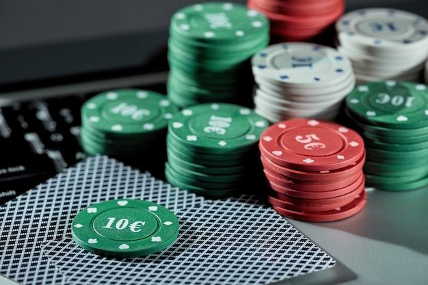 Visualização de fichas e cartões de cassino em um laptop para jogar online. conceito de jogos de azar online, pôquer, cassino virtual.
