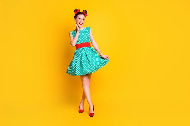 Visualização do comprimento total do corpo de uma bela garota magra e alegre, usando um vestido azul-petróleo, curtindo uma caminhada isolada sobre um fundo de cor amarela brilhante