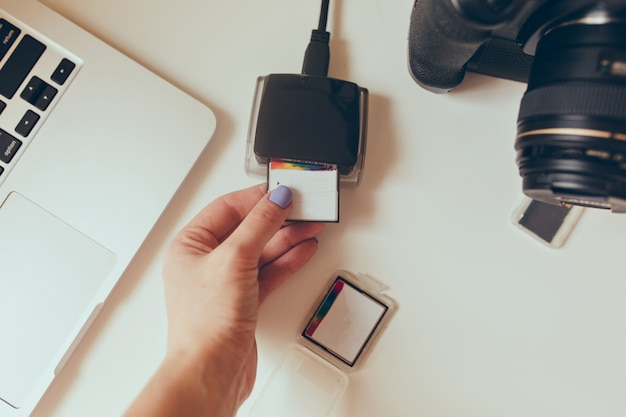 Visualização do estúdio de design de mesa de trabalho, processo de upload de fotos de sua unidade flash em um computador. câmera profissional cercada, lentes, laptop, pen drives.