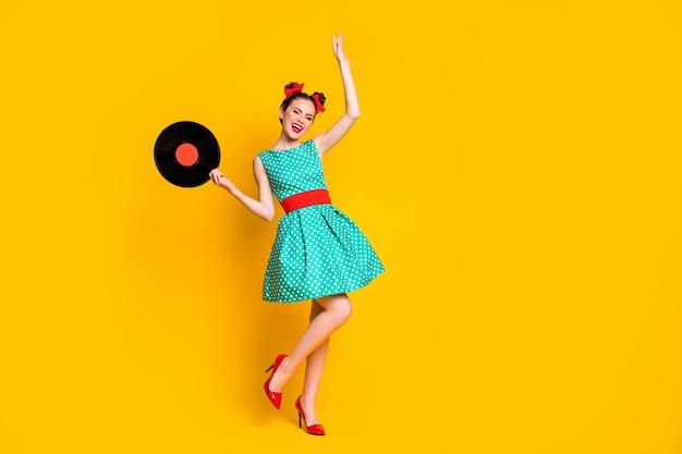 Visualização do tamanho do corpo de uma garota muito alegre segurando nas mãos o disco de vinil, dançando, descansando isolado no fundo de cor amarela brilhante