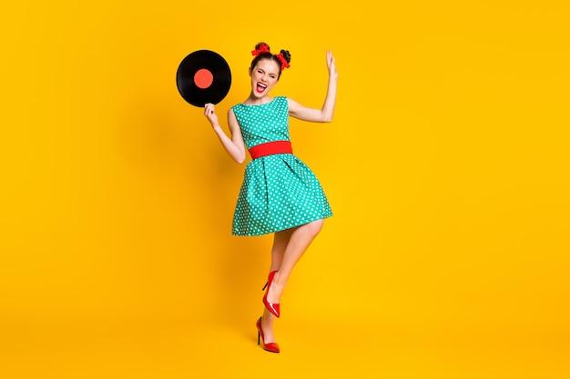 Visualização do tamanho total do corpo de uma bela garota alegre segurando nas mãos um disco de vinil, dançando se divertindo, isolado no fundo de cor amarela brilhante