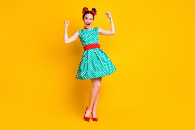 Visualização do tamanho total do corpo de uma bela garota alegre usando um vestido azul-petróleo, se divertindo, comemorando isolado no fundo de cor amarela brilhante