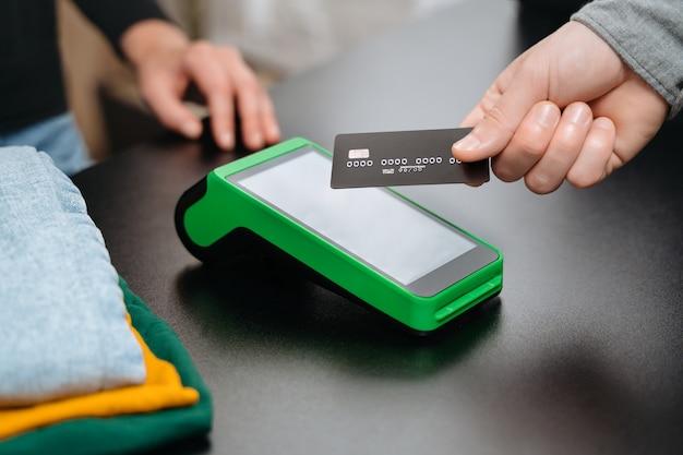 Visualização em close, cliente do sexo masculino usando cartão de crédito do banco para pagamento sem contato pelo terminal nfc no balcão enquanto faz compras na loja de roupas