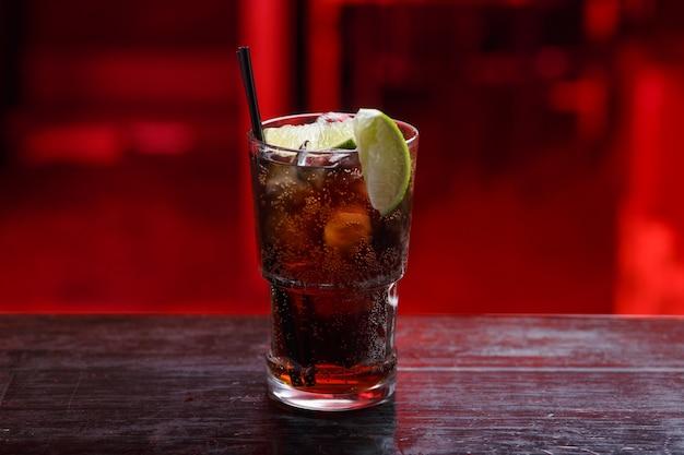 Visualização horizontal. close de um coquetel cuba libre em copo longo, gim, em pé no balcão do bar, isolado em um espaço vermelho.