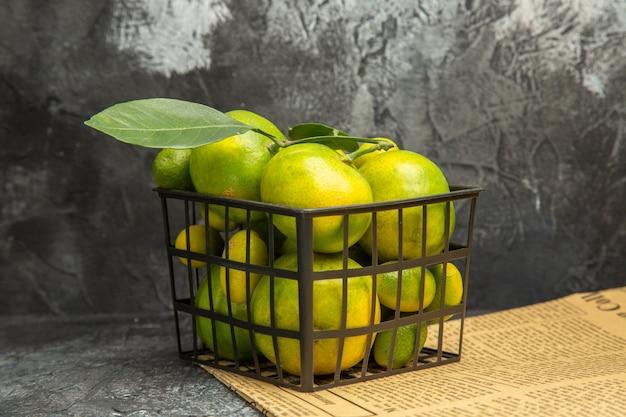 Visualização horizontal da cesta preta com tangerinas verdes frescas e kumquats em jornais na mesa cinza