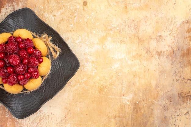 Visualização horizontal da mesa posta para a hora do café e do chá com framboesas em bolos na mesa de cores misturadas