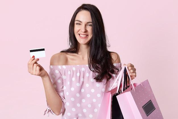 Visualização horizontal da mulher morena feliz com expressão de prazer, carrega sacolas de compras e cartão de plástico, se alegra de ter dinheiro suficiente