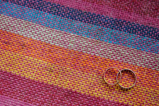 Visualização horizontal de alianças de casamento em tecido colorido