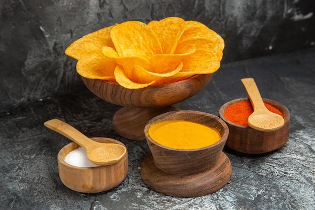 Visualização horizontal de batatas fritas crocantes decoradas em forma de flor e diferentes especiarias na mesa cinza