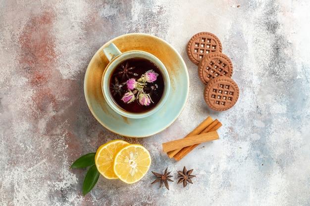 Visualização horizontal de biscoitos de chá de ervas e rodelas de limão e limão com canela na mesa branca