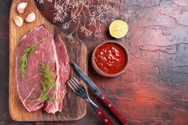 Visualização horizontal de carne vermelha em uma tábua de madeira e ketchup em uma tigela pequena garfo e faca de limão em fundo escuro