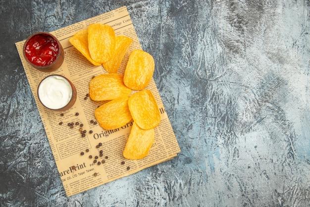 Visualização horizontal de deliciosas batatas fritas caseiras e ketchup de maionese na tigela de pimenta no jornal na mesa cinza