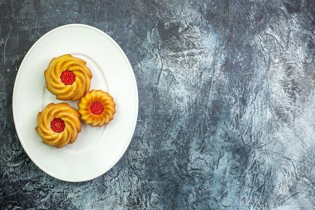 Visualização horizontal de deliciosos biscoitos em um prato branco do lado direito em uma superfície escura