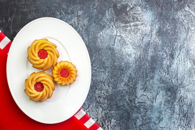 Visualização horizontal de deliciosos biscoitos em um prato branco em uma toalha vermelha em uma superfície escura