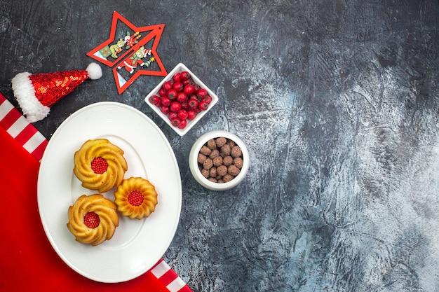 Visualização horizontal de deliciosos biscoitos em um prato branco na toalha vermelha e cornel do chapéu de papai noel e chocoltes em potes brancos na superfície escura
