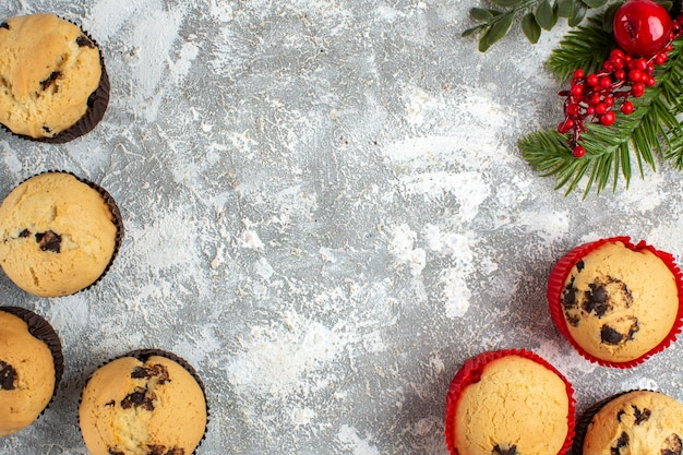 Visualização horizontal de deliciosos bolinhos pequenos com galhos de chocolate e pinheiro na superfície do gelo