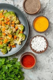 Visualização horizontal de especiarias diferentes de salada de vegetais saudáveis e um monte de verde na mesa branca