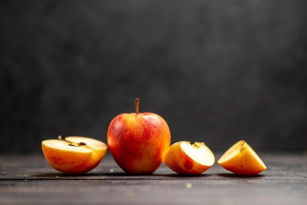 Visualização horizontal de maçãs frescas naturais picadas e vermelhas inteiras em fundo preto