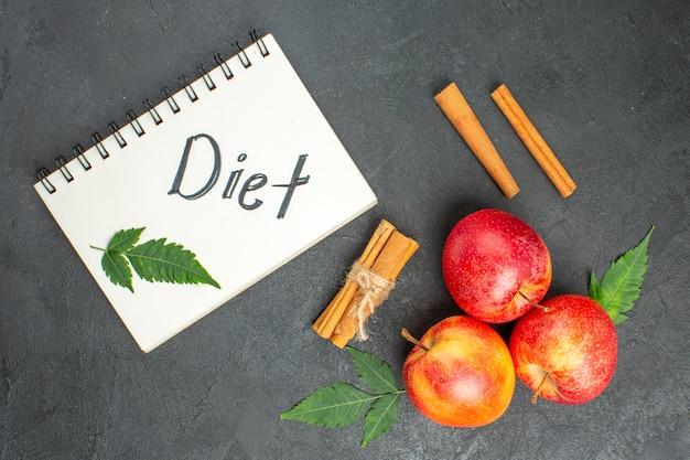 Visualização horizontal de maçãs frescas orgânicas naturais com folhas verdes, caderno de limão e canela com inscrição de dieta em fundo preto