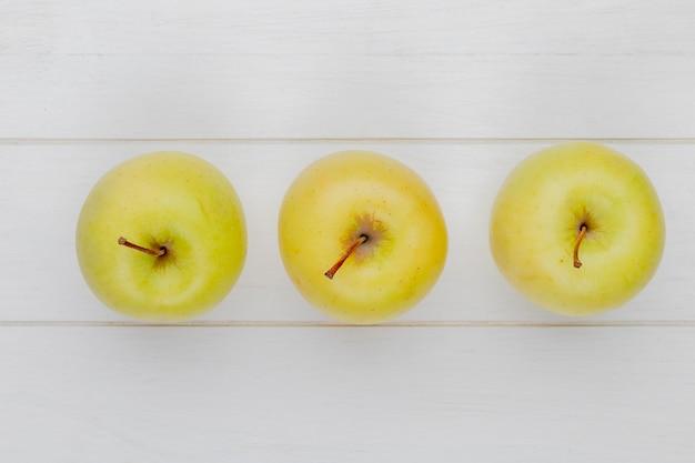 Visualização horizontal de maçãs verdes em fundo de madeira