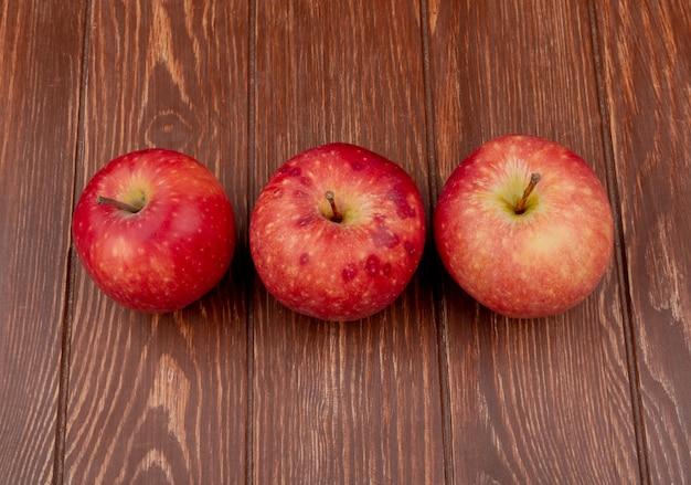 Visualização horizontal de maçãs vermelhas em fundo de madeira