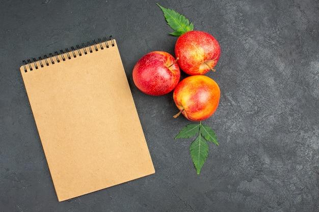 Visualização horizontal de maçãs vermelhas frescas com folhas e caderno espiral em fundo preto