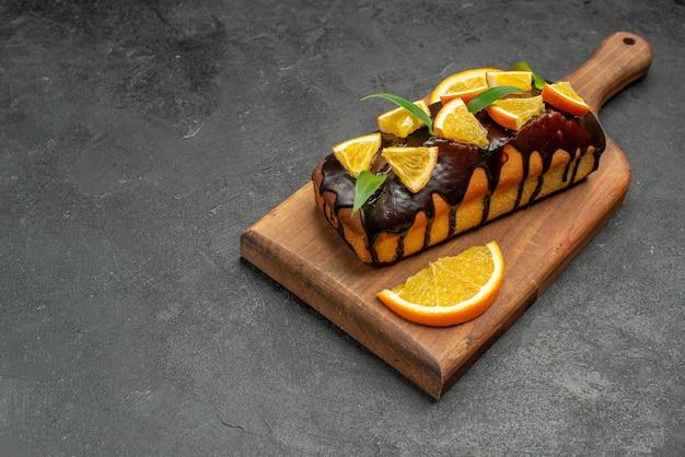 Visualização horizontal de saborosos bolos decorados com laranjas e chocolate em uma tábua na mesa preta