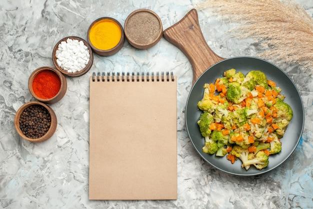 Visualização horizontal de salada de vegetais saudáveis, diferentes especiarias e caderno na mesa branca