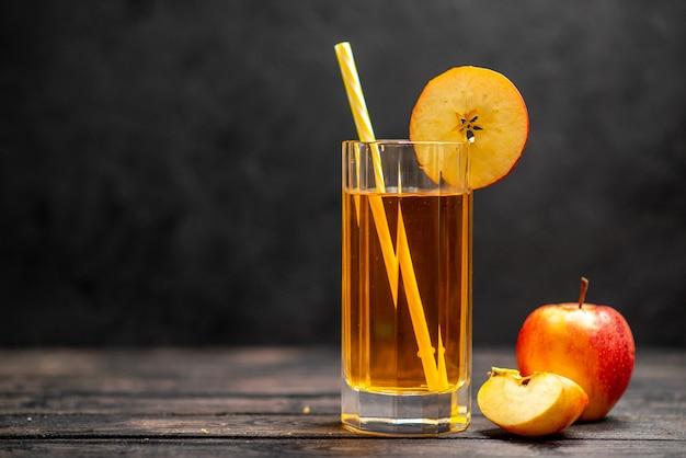 Visualização horizontal de suco fresco natural delicioso em dois copos com limão de maçã vermelha em fundo preto