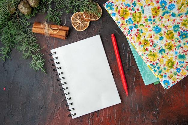 Visualização horizontal de um caderno fechado com caneta canela, limão, uma bola de corda e livros em fundo escuro